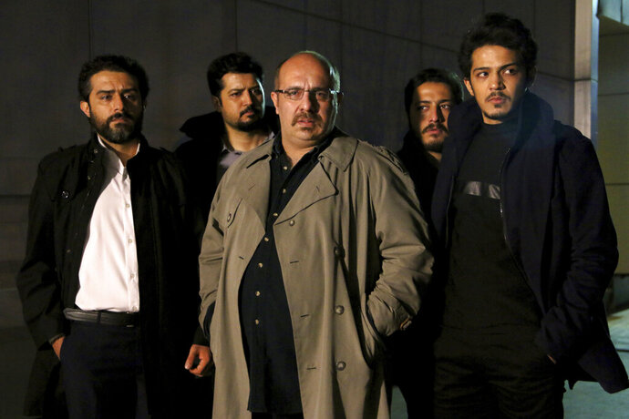 "This undated promotional handout still from the Iranian state TV series, ""Gando,"" shows actor Payam Dehkordi, center, who plays a character apparently based on Washington Post journalist Jason Rezaian, among other actors. The new Iranian television series is glorifying the hard-liners and intelligence officers behind the 2014 arrest and imprisonment of Rezaian. (Mohammad Bagheri/TV series, ""Gando,"" via AP)"