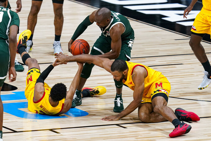 Michigan State guard Joshua Langford (1) grabs a loose ball over Maryland guard Aaron Wiggins (2) and forward Galin Smith (30) in the second half of an NCAA college basketball game at the Big Ten Conference tournament in Indianapolis, Thursday, March 11, 2021. (AP Photo/Michael Conroy)