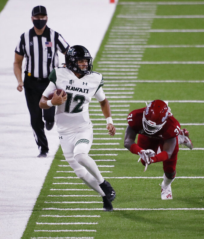 Hawaii quarterback Chevan Cordeiro (12) takes off for a big gain against Fresno State defensive end Andrew Wright during the second half of an NCAA college football game in Fresno, Calif., Saturday, Oct. 24, 2020. (AP Photo/Gary Kazanjian)