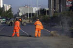 Afghan Municipality workers sweep a road after bomb explosion that targeted a bus carrying local TV station employees in Kabul, Afghanistan, Saturday, May 30, 2020. (AP Photo/Rahmat Gul)