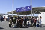 Migrants wait outside the new closed monitored facility in Zervou village, on the eastern Aegean island of Samos, Greece, Monday, Sept. 20, 2021. The transfer of the migrants to the new, €43 million ($50 million) facility began Monday and be completed by Wednesday. (AP Photo/Michael Svarnias)