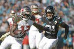 Tampa Bay Buccaneers wide receiver Chris Godwin, left, runs after a reception past Jacksonville Jaguars cornerback A.J. Bouye (21) during the first half of an NFL football game, Sunday, Dec. 1, 2019, in Jacksonville, Fla. (AP Photo/Phelan M. Ebenhack)