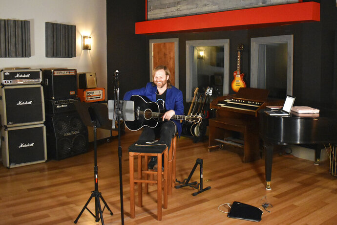 In this March 31, 2020 photo provided by Sean Giovanni, Benji Harris, an artist/songwriter and client executive for a company called Song Division, leads a virtual songwriting team building workshop for a corporate client at The Record Shop, a recording studio in Nashville, Tenn., owned by Sean Giovanni. Giovanni got an important lesson that will help his business long after the pandemic has subsided. The Record Shop doesn't have to be limited to what it can produce onsite.  (Sean Giovanni via AP)