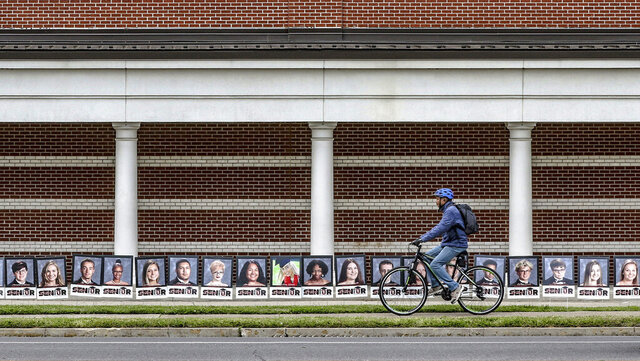 A bicyclist rides past senior graduate portraits that have been lined up along the front of Owensboro High School in recognition of the school's 2020 graduating class, Tuesday, May 12, 2020, in Owensboro, Ky. (Greg Eans/The Messenger-Inquirer via AP)