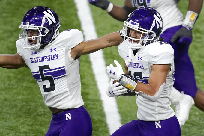 Northwestern defensive back Brandon Joseph, right, celebrates with teammate JR Pace (5) after intercepting a pass in the end zone during the first half of the Big Ten championship NCAA college football game against Ohio State, Saturday, Dec. 19, 2020, in Indianapolis. (AP Photo/Darron Cummings)