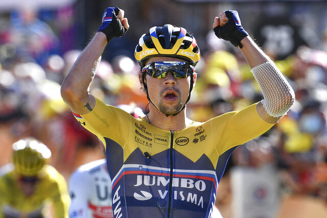 Slovenia's Primoz Roglic celebrates as he crosses the finish line to win the fourth stage of the Tour de France cycling race over 160,5 kilometers (99,7 miles) with start in Sisteron and finish in Orcieres-Merlette, southern France, Tuesday, Sept.1, 2020. (Anne-Christine Poujoulat, Pool via AP)