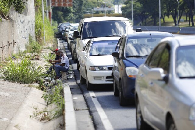 Men sit on a curb alongside vehicles lined up to enter a gas station during a nation-side fuel crunch, in Caracas, Venezuela, Wednesday, Sept 30, 2020. (AP Photo/Ariana Cubillos)
