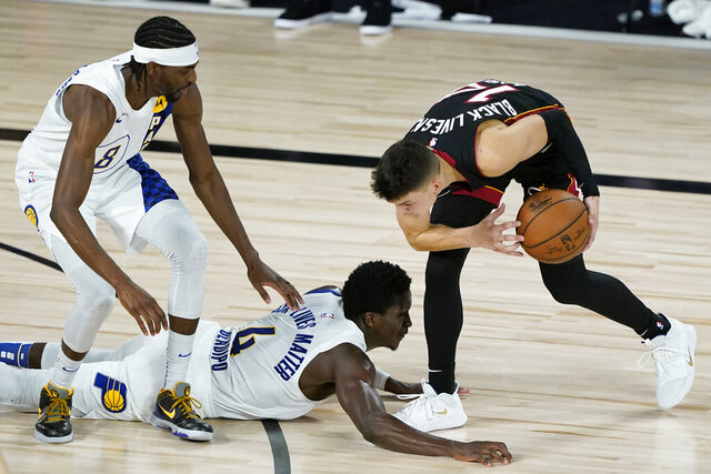 Indiana Pacers' Justin Holiday, left, Victor Oladipo, center, and Miami Heat's Tyler Herro (14) scramble for the ball during the second half of an NBA basketball first round playoff game Monday, Aug. 24, 2020, in Lake Buena Vista, Fla. (AP Photo/Ashley Landis, Pool)