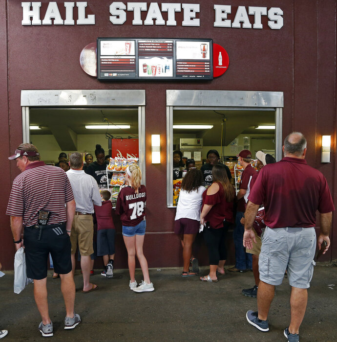 In this Sept. 1, 2018, photo, fans work their way to the snack bar where discounted prices await them at Davis Wade Stadium at Mississippi Stare, prior to their NCAA college football game against Stephen F. Austin in Starkville, Miss. The SEC saw a drop of more than 2,400 fans per game last season, which was the biggest decline of any Power Five conference. And in an effort to attract and keep more fans, Mississippi State dropped prices of some concessions, as one of the fan enticements. (AP Photo/Rogelio V. Solis)