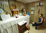 In this Aug. 9, 2019, photo Marge Ruminski, from Parma, Ohio, sits in the chair where Rhoda Wise was visited by Jesus Christ in front of the altar in Canton, Ohio. (AP Photo/Tony Dejak)