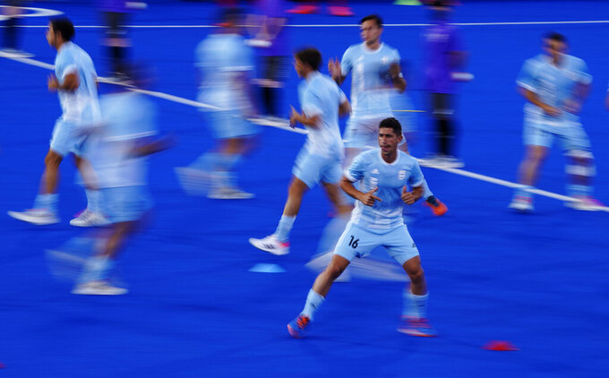 Argentina players warm up before a men's field hockey match against Japan at the 2020 Summer Olympics, Sunday, July 25, 2021, in Tokyo, Japan. (AP Photo/John Locher)