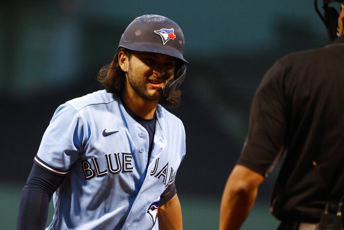 Toronto Blue Jays' Bo Bichette looks back at the umpire after being called out on strikes during the first inning of a baseball game Tuesday, April 20, 2021, at Fenway Park in Boston. (AP Photo/Winslow Townson)