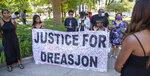 A banner, signed by community members, is held during a press conference to announce federal charges on behalf of the family of Dreasjon Reed, Tuesday, June 16, 2020 in Indianapolis. Reed was fatally shot by an Indianapolis police officer. (Robert Scheer/The Indianapolis Star via AP)
