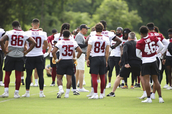 FILE - Washington Football Team head coach Ron Rivera, center, talks to his players during an NFL football practice at Inova Sports Performance Center in Ashburn, Va., in this Thursday, June 10, 2021, file photo. The NFL has fined the Washington Football Team $10 million and owner Dan Snyder is stepping away from day-to-day operations after an independent investigation into the organization's workplace misconduct. The team was not stripped of any draft picks as part of the league's discipline that was announced Thursday, July 1, 2021. (AP Photo/Luis M. Alvarez, File)