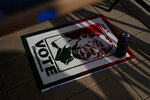 A campaign poster sits on the ground near where artist Brandon Litman, 39, of Brooklyn, N.Y., spray paints more posters after Georgia's Senate runoff race on Saturday, Jan. 9, 2021, in Atlanta. (AP Photo/Brynn Anderson)