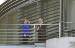German Chancellor Angela Merkel and Britain's Prime Minister Boris Johnson talk as they stand on a balcony prior to a dinner as part of a meeting at the Chancellery in Berlin, Germany, Wednesday, Aug. 21, 2019. (AP Photo/Michael Sohn)