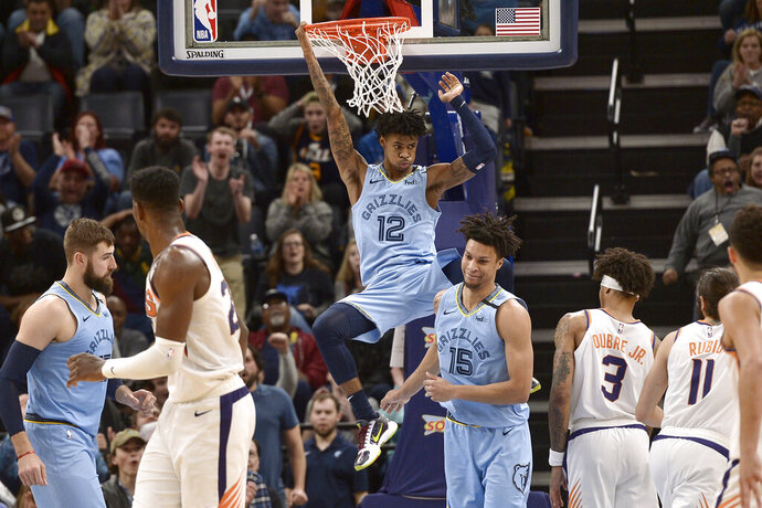 Memphis Grizzlies guard Ja Morant (12) hangs from the rim after a dunk in the second half of an NBA basketball game against the Phoenix Suns Sunday, Jan. 26, 2020, in Memphis, Tenn. (AP Photo/Brandon Dill)