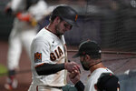 San Francisco Giants' Daniel Robertson, left, is congratulated by manager Gabe Kapler after scoring against the Colorado Rockies during the fifth inning of a baseball game in San Francisco, Tuesday, Sept. 22, 2020. (AP Photo/Jeff Chiu)