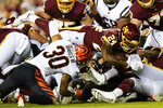 Washington Football Team running back Antonio Gibson (24) lunges for yardage as he is tackled by Cincinnati Bengals free safety Jessie Bates (30) during the first half of a preseason NFL football game Friday, Aug. 20, 2021, in Landover, Md. (AP Photo/Susan Walsh)