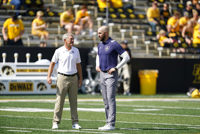 Iowa head coach Kirk Ferentz, left, talks with Kent State head coach Sean Lewis before an NCAA college football game, Saturday, Sept. 18, 2021, in Iowa City, Iowa. (AP Photo/Charlie Neibergall)