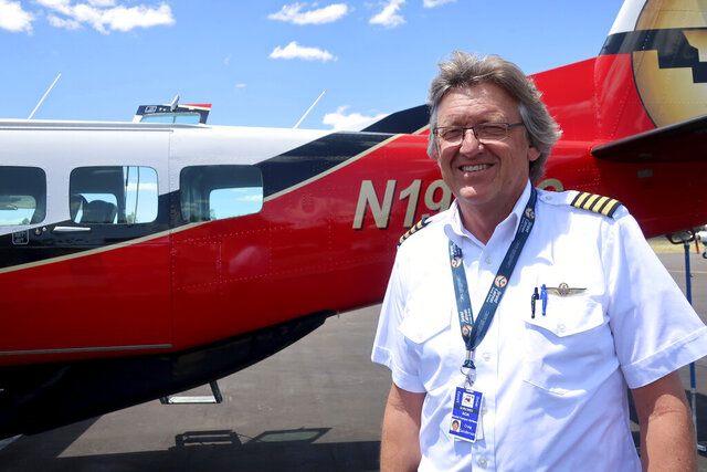 This Tuesday, July 28, 2020 photo shows Tusayan, Ariz., Mayor Craig Sanderson posing outside the aircraft he flies for tours over the Grand Canyon in northern Arizona. About 240 residents of Tusayan are registered to vote in the primary election that will decide the mayoral race Tuesday, Aug. 4, 2020. (AP Photo/Felicia Fonseca)