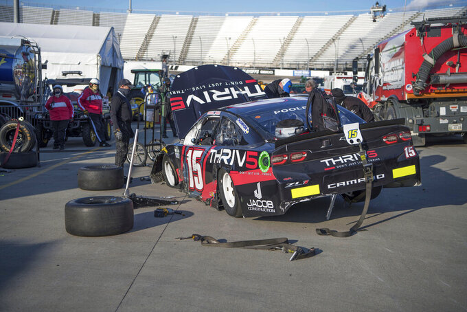 Pit crew for Brennan Poole (15) work on his car in the garage area during a NASCAR Cup Series auto race at the Martinsville Speedway in Martinsville, Va., Sunday, Nov. 1, 2020. (AP Photo/Lee Luther Jr.)