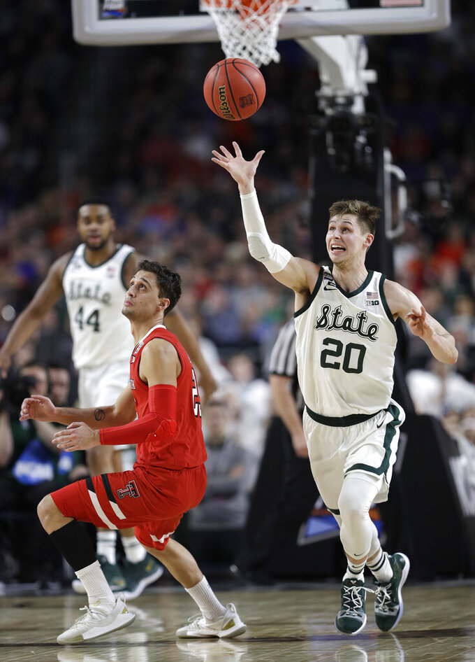 Michigan State guard Matt McQuaid runs down a loose ball over Texas Tech guard Davide Moretti during the first half in the semifinals of the Final Four NCAA college basketball tournament, Saturday, April 6, 2019, in Minneapolis. (AP Photo/David J. Phillip)