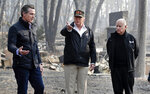 FILE - In this Nov. 17, 2018, file photo, President Donald Trump talks with then Gov.-elect Gavin Newsom, left, and as California Gov. Jerry Brown listens during a visit to a neighborhood impacted by the wildfires in Paradise, Calif. California Gov. Gavin Newsom says the Trump administration is engaging in