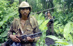FILE - In this Aug. 1986, file photo, a Sandinista soldier walks warily through the jungle on a patrol to hunt U.S.-backed contra rebels near Zompopera in northern Nicaragua. There is increasing concern for the safety of journalists covering protests at state capitals across the U.S., and in Washington. Packing a gas mask and helmet has become the new normal. It's starting to look, just a bit, like what foreign correspondents face in the world's conflict zones. (AP Photo/Andrew Selsky, File)