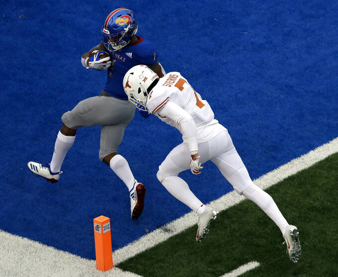 Kansas running back Pooka Williams Jr. (1) scores a touchdown while covered by Texas defensive back Caden Sterns (7) during the second half of an NCAA college football game in Lawrence, Kan., Friday, Nov. 23, 2018. (AP Photo/Orlin Wagner)