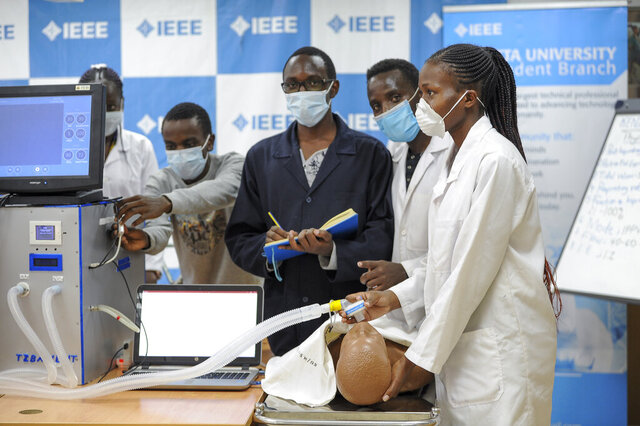 In this photo taken Monday, April 13, 2020, medical students test a self-designed computer-controlled ventilator prototype at the Chandaria Business and Incubation Centre of Kenyatta University in Nairobi, Kenya. Researchers across Africa are looking for ways to make their own ventilators, protective equipment and hand sanitizers as the continent faces a peak in coronavirus cases long after the United States and European countries have bought up global supplies during the pandemic. (AP Photo/John Muchucha)