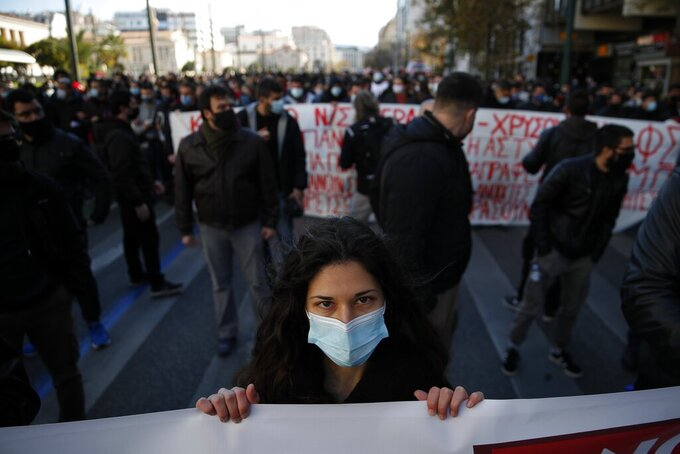 A university student holds a banner during a rally against education reforms in Athens, Thursday, Jan. 28, 2021. Thousands of protesters in Greece have held demonstrations in the Greek capital and the second largest city of Thessaloniki against proposed education reforms, defying a weeklong public ban on protests imposed as part of measures to tackle the coronavirus pandemic. (AP Photo/Thanassis Stavrakis)
