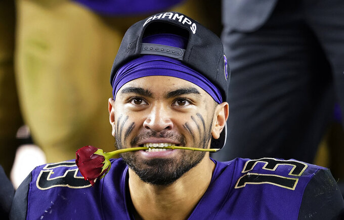 Washington linebacker Brandon Wellington holds a rose in his mouth as he celebrates with teammates after Washington defeated Utah 10-3 in the Pac-12 Conference championship NCAA college football game in Santa Clara, Calif., Friday, Nov. 30, 2018. (AP Photo/Tony Avelar)
