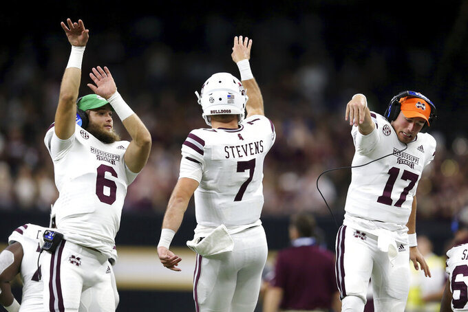 Mississippi State quarterback Tommy Stevens (7) celebrates his second-quarter touchdown run with quarterbacks Garrett Shrader (6) and Logan Burnett (17) during an NCAA college football game against Louisiana-Lafayette in New Orleans, Saturday, Aug. 31, 2019. (AP Photo/Chuck Cook)
