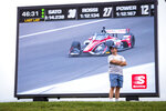 A fan watches the action on the track during a practice session for the IndyCar auto race at Indianapolis Motor Speedway, Friday, Aug. 13, 2021, in Indianapolis. (AP Photo/Doug McSchooler)