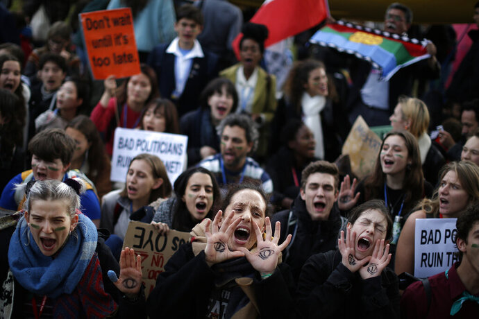 People shout slogans during a march organized by the Fridays for Future international movement of school students outside of the COP25 climate talks congress in Madrid, Spain, Friday, Dec. 13, 2019. The United Nations Secretary-General has warned that failure to tackle global warming could result in economic disaster. (AP Photo/Manu Fernandez)