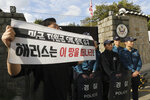 In this Friday, Oct. 18, 2019, photo, a college student holds a banner in front of the U.S. ambassador's residence in Seoul, South Korea. South Korean police said Saturday, Oct. 19, they beefed up security at the U.S. ambassador's residence in Seoul after a group of anti-American students used ladders to break into the compound. The sign reads