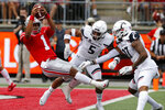 Ohio State quarterback Justin Fields, left, dives over the goal line past Cincinnati defensive back Darrick Forrest, center, and linebacker Dorian Holloway during the first half of an NCAA college football game Saturday, Sept. 7, 2019, in Columbus, Ohio. (AP Photo/Jay LaPrete)