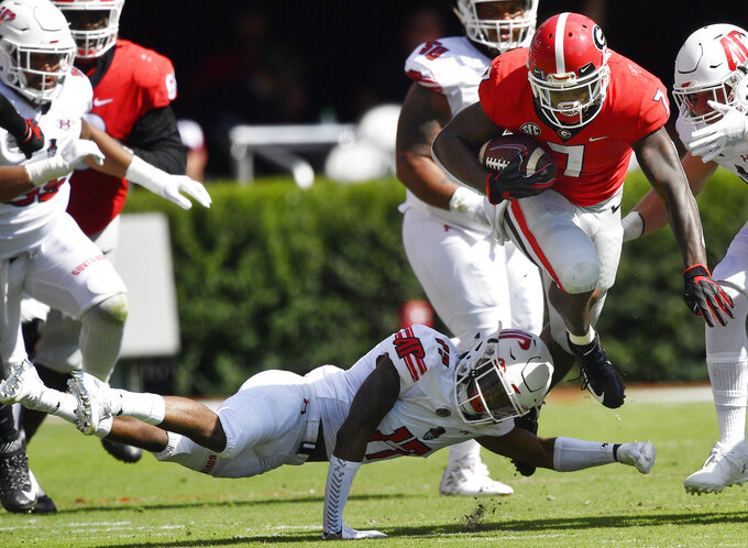 Georgia running back D'Andre Swift (7) runs by Austin Peay defensive back Rashon Davis (17)during the first half of an NCAA college football game, Saturday, Sept. 1, 2018, in Athens, Ga. (AP Photo/Mike Stewart)