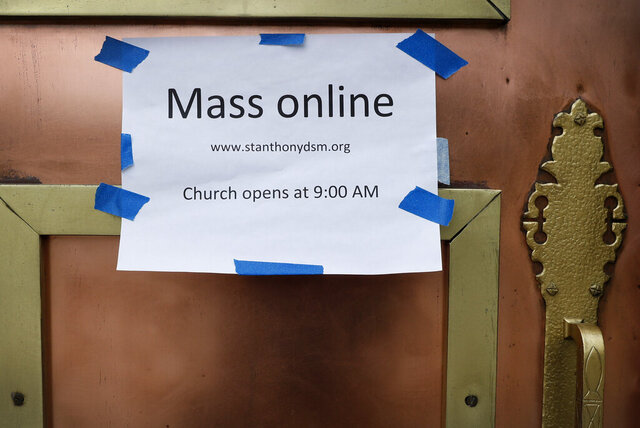 A sign on the front door of the St. Anthony's Catholic Church directs parishioners to the availability of online mass, Friday, March 27, 2020, in Des Moines, Iowa. Daily masses continue to be available online in response to the new coronavirus outbreak but the church is open daily for private prayers. (AP Photo/Charlie Neibergall)