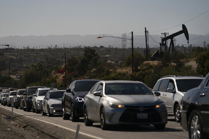 Motorists wait for a signal to change as pump jacks extract oil at the Inglewood Oil Field, Thursday, June 10, 2021, in Los Angeles. (AP Photo/Jae C. Hong)