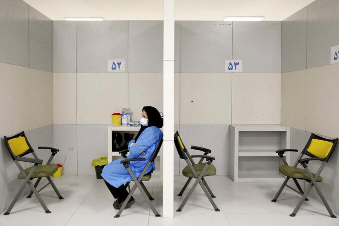 A medic waits to administer Sinopharm COVID-19 vaccine shots, at the Iran Mall shopping center in Tehran, Iran, Monday, May 17, 2021. (AP Photo/Ebrahim Noroozi)