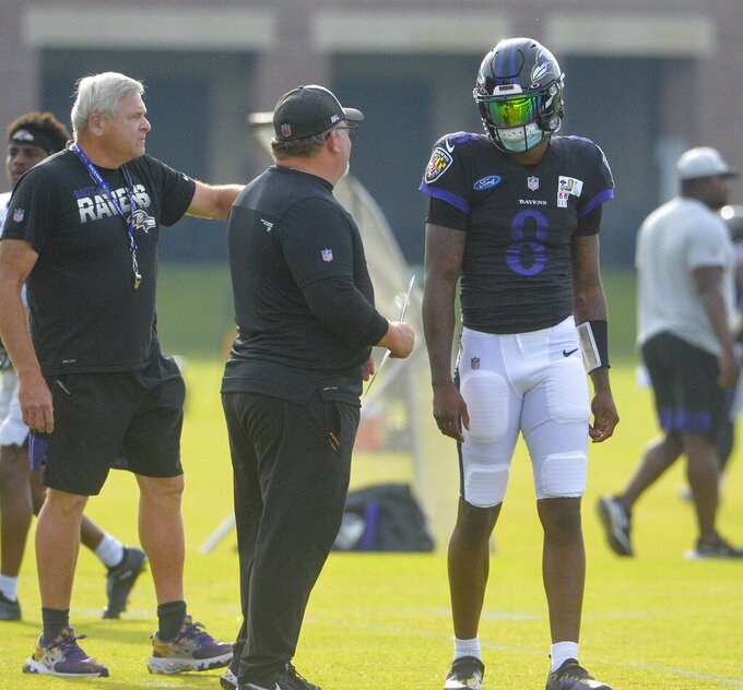 Baltimore Ravens quarterback Lamar Jackson, right, is greeted by offensive coordinator Greg Roman at the start practice during training camp at Under Armour Performance Center on Sunday, Aug. 7, 2021 in Owings Mills, Md. (Kevin Richardson/The Baltimore Sun via AP)