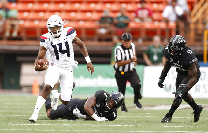 Arizona quarterback Khalil Tate (14) runs through the Hawaii defense during the second quarter during an NCAA college football game, Saturday, Aug. 24, 2019, in Honolulu. (AP Photo/Marco Garcia)