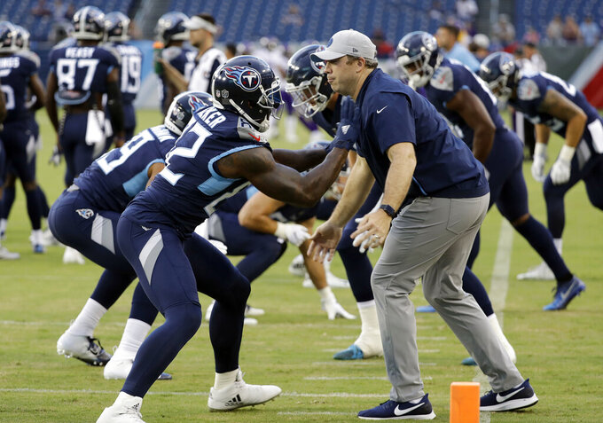 "File-This Aug. 30, 2018, file photo shows Tennessee Titans tight ends coach Arthur Smith, right, helping tight end Delanie Walker (82) warm up before a preseason NFL football game in Nashville, Tenn. Mike Vrabel has stayed inside the Tennessee Titans' organization for his new offensive coordinator, promoting tight ends assistant Smith to the job vacated when Matt LaFleur left for the Green Bay Packers' head coaching job. Vrabel announced the promotion Monday, jan. 21, 2019, saying he's excited for both Smith and the Titans to promote a ""deserving coach.""(AP Photo/James Kenney, File)"