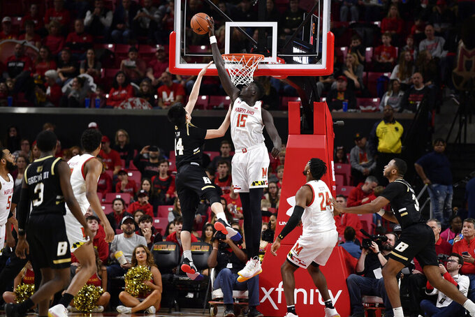 Maryland center Chol Marial (15) blocks a shot by Bryant guard Benson Lin (14) during the second half of an NCAA college basketball game, Sunday, Dec. 29, 2019, in College Park, Md. (AP Photo/Brien Aho)