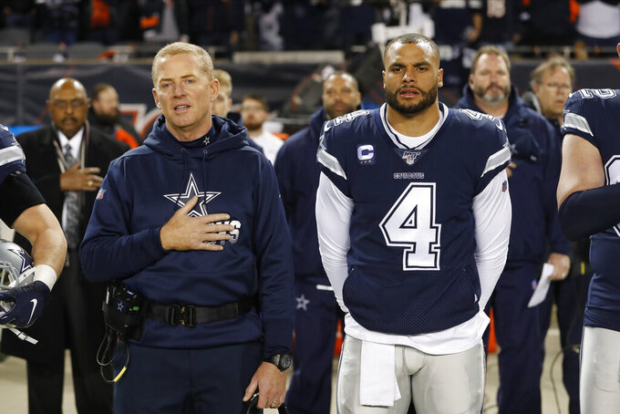 "FILE - In this Dec. 5, 2019, file photo, Dallas Cowboys coach Jason Garrett and quarterback Dak Prescott (4) listen to the national anthem before the team's NFL football game against the Chicago Bears in Chicago.  Prescott wants his teammates to decide for themselves whether to protest during the national anthem. Defensive lineman Tyrone Crawford says they have the ""green light"" to do so. Owner Jerry Jones hasn't said in so many words, but it appears his hard-line stance over his players standing during the anthem has eased amid a national reckoning over racial justice. (AP Photo/Charles Rex Arbogast, File)"