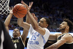 North Carolina's Garrison Brooks (15) pulls in a rebound against Wake Forest's Jahcobi Neath (4) and Olivier Sarr (30) during the second half of an NCAA college basketball game in Chapel Hill, N.C., Tuesday, March 3, 2020. (AP Photo/Chris Seward)