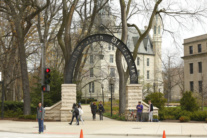 In this Friday, April 29, 2016, photo, people stand near the entrance gate to Northwestern University in Evanston, Ill. Northwestern University's student newspaper is under fire. Their first critics came from within the campus as student activists questioned journalists' coverage of protests. Within days, editors decided to write a statement apologizing but their editorial prompted a second round of criticism from journalists around the country starting Monday, Nov. 11, 2019.  (Chris Walker/Chicago Tribune via AP)