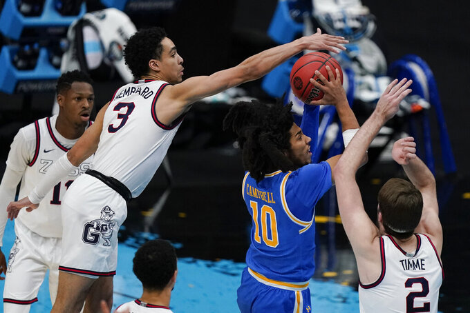 UCLA guard Tyger Campbell (10) drives to the basket between Gonzaga guard Andrew Nembhard (3) and forward Drew Timme (2) during the second half of a men's Final Four NCAA college basketball tournament semifinal game, Saturday, April 3, 2021, at Lucas Oil Stadium in Indianapolis. (AP Photo/Michael Conroy)